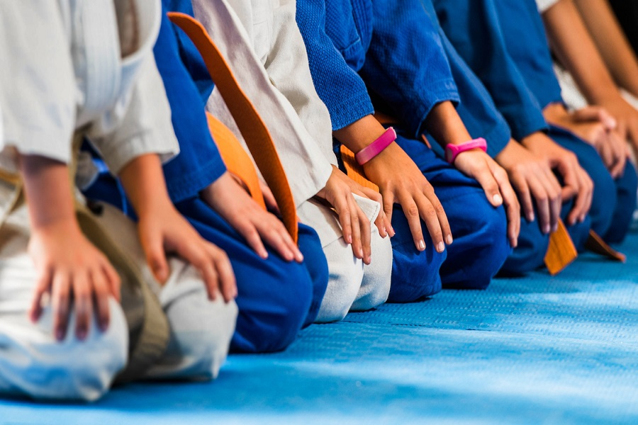 Unrecognizable children sitting in a row on karate training.
